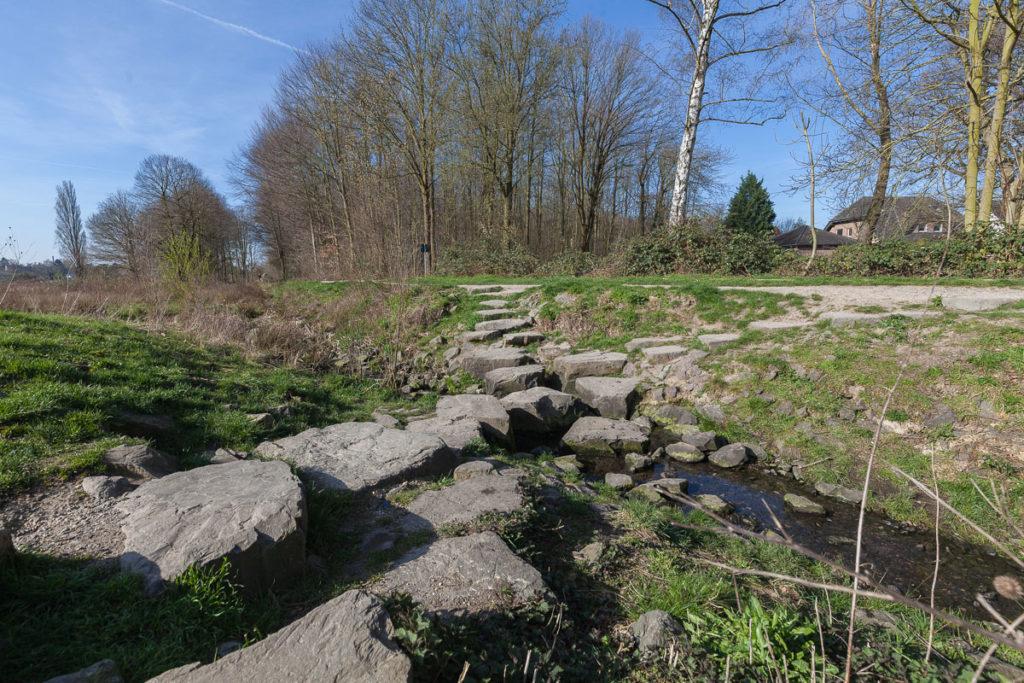 """Nur wenige Meter von der Straße """"An den Zwölf Morgen"""" entfernt kann der Bungtbach über diese Findlinge überquert werden."""